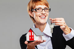 Friendly female real estate agent offering a house and keys Royalty Free Stock Images