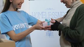 Friendly female volunteer presenting gift box for poor woman in charity center stock video