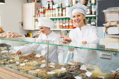 Friendly females staff offering nuts. In shop Royalty Free Stock Photography