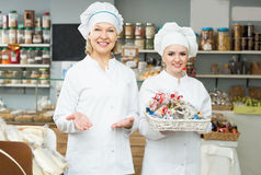 Friendly females staff offering sweets. In local confectionery Royalty Free Stock Photos