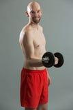 Friendly fitness man holding dumbbell Stock Images