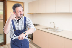 Friendly fitter showing call sign. While holding wrench as appointment concept and text space Stock Photos