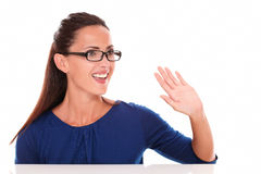 Friendly girl with glasses gesturing a greeting Stock Photos
