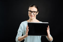 Friendly girl holding tablet before herself Stock Photos