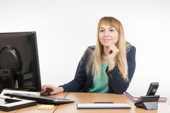 The friendly girl looked up at the office visitor. Young woman secretary sitting at office desk working, isolated on white background Stock Photos