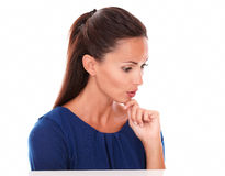 Friendly girl looking down with hand on chin. In white background - copyspace Royalty Free Stock Photos