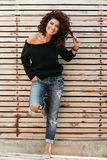 Friendly girl over wooden wall. Beautiful friendly girl with curly hair wearing black sweater and jeans posing against wooden wall and smiling, full length Stock Photography