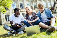 Friendly groupmates doing university project together. Dream team. Three joyful students relaxing on grass and smiling while focusing their attention on a screen Stock Images