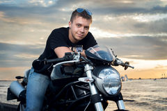 Friendly guy on a motorcycle smiling at the camera Royalty Free Stock Photos
