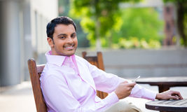 Friendly guy using cellphone. Closeup portrait, young happy businessman sitting, checking his cellphone, isolated on background of a city building, trees, on a Stock Photo