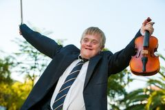 Friendly handicapped boy raising violin outdoors. Stock Photography