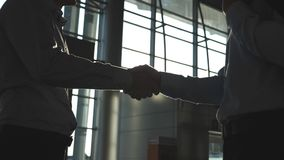 Friendly handshake of two businessmen greeting each other in the office. Business handshake indoor. Shaking of male arms. At the building. Colleagues meet and stock footage