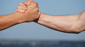Friendly handshake of two unrecognizable muscular white men on blue sky background. Shaking of male arms outdoor. Two stock video