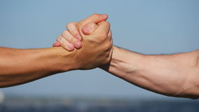 Friendly handshake of two unrecognizable muscular white men on blue sky background. Shaking of male arms outdoor. Two stock footage