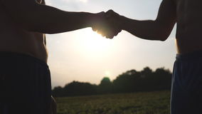 Friendly handshake of two unrecognizable muscular white men with sun shine at background. Shaking of male arms outdoor. Two strong guy meeting outside stock footage