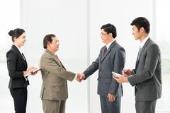 Friendly handshaking Stock Images