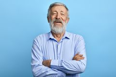 Friendly handsome man standing with crossed arms, laughing at something royalty free stock image