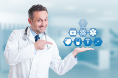 Friendly handsome medic holding digital buttons with medical ico Stock Images