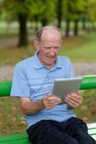Friendly handsome old man with tablet  pc Stock Photo