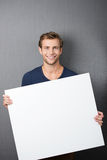 Friendly handsome young man with a blank sign royalty free stock image