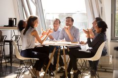 Friendly happy diverse workers laughing eating pizza together in. Friendly happy diverse team workers talking laughing eating pizza together in office, cheerful stock photo