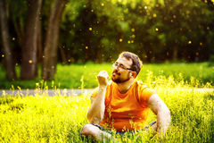 Friendly happy man is sitting with closed eyes in green park. Friendly happy man is sitting with closed eyes in fresh green park grass at sunny summer trees Stock Photos