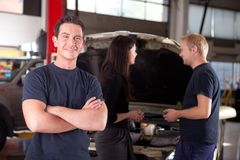Friendly Happy Mechanic. Portrait of a mechanic looking at the camera with a customer and second mechanic in the background Royalty Free Stock Photo