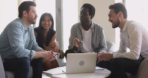 Friendly happy multiethnic business team talking working together with laptop
