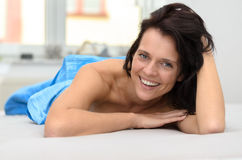 Friendly happy young woman lying on her bed stock images