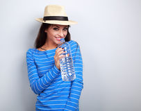 Friendly healthy woman in summer hat drinking still water on blu. E background Stock Images