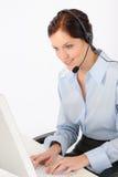 Friendly help desk woman typing computer. Friendly help desk woman at call center sitting behind computer Stock Photos