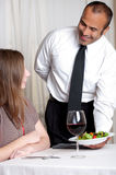 Friendly Hispanic Waiter serves lunch Royalty Free Stock Photography