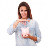 Friendly hispanic woman with her coin bank Royalty Free Stock Photography