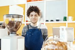 Friendly hospitable barista smiling and standing behind bar counter. royalty free stock photos