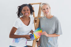 Friendly housemates choosing colour for wall looking at camera Stock Images