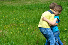 Friendly hug. Older brother calms his younger brother hugging Stock Image
