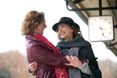 Friendly Hug at Train Station. Friendly hug from two european women at an outdoor train station platform Royalty Free Stock Photo