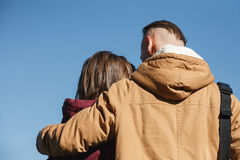 Friendly hug. Young male hugging female looking at her rear view blue sky on background Royalty Free Stock Photos