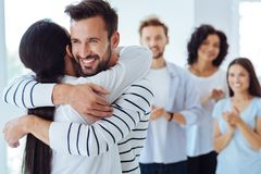 Positive happy people hugging each other. Friendly hugs. Positive joyful nice people smiling and hugging each other while standing together Stock Images