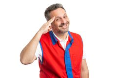 Hypermarket employee making military greeting with hand. Friendly hypermarket or supermarket male employee making military greeting gesture by touching temple stock photos