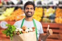 Supermarket employee holding grocery bag with thumb up. Friendly indian male supermarket or hypermarket employee holding brown paper grocery bag with thumb up as stock image