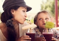 Friendly kid girl and fun emotional mother drinking berries smoo Stock Photography