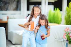 Friendly kid girl and fun emotional mother drinking berries smoothie juice together in street cafe and looking on each. Other. Closeup portrait royalty free stock images