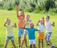 Friendly kids jumping together in park on summer. Friendly kids in school age jumping together in park on summer Royalty Free Stock Image