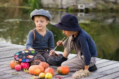 Friendly kids paint small Halloween pumpkins. On the river bank Royalty Free Stock Photography