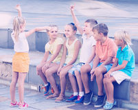 Friendly kids playing charades outdoors. Friendly kids in school age playing charades outdoors Stock Image