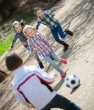 Friendly kids playing street football outdoors Royalty Free Stock Photo