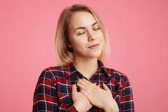 Friendly kind hearted female keeps eyes shut, hands on chest, expresses her gratitude to someone, poses against pink background. A. Dorable beautiful young woman stock images