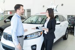Adviser Showing Right Car For Customer At The Right Price. Friendly and knowledgeable adviser showing car to businessman as per his desire royalty free stock photos