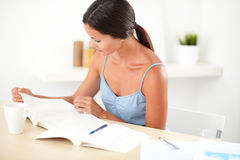 Friendly latin female reading her books Stock Photo